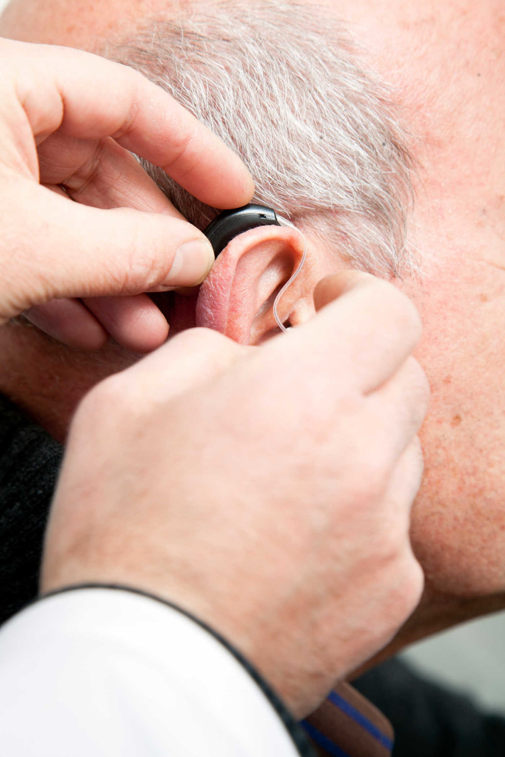 A doctor assiting patient with hearing aid application