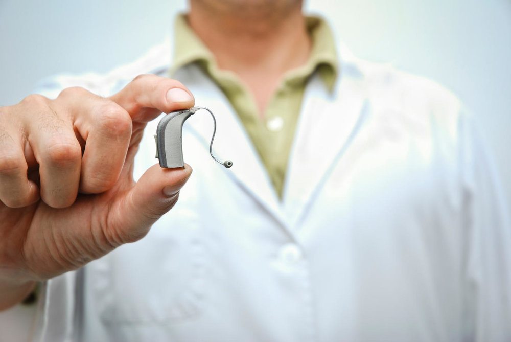 Close up of a doctor holding a hearing aid