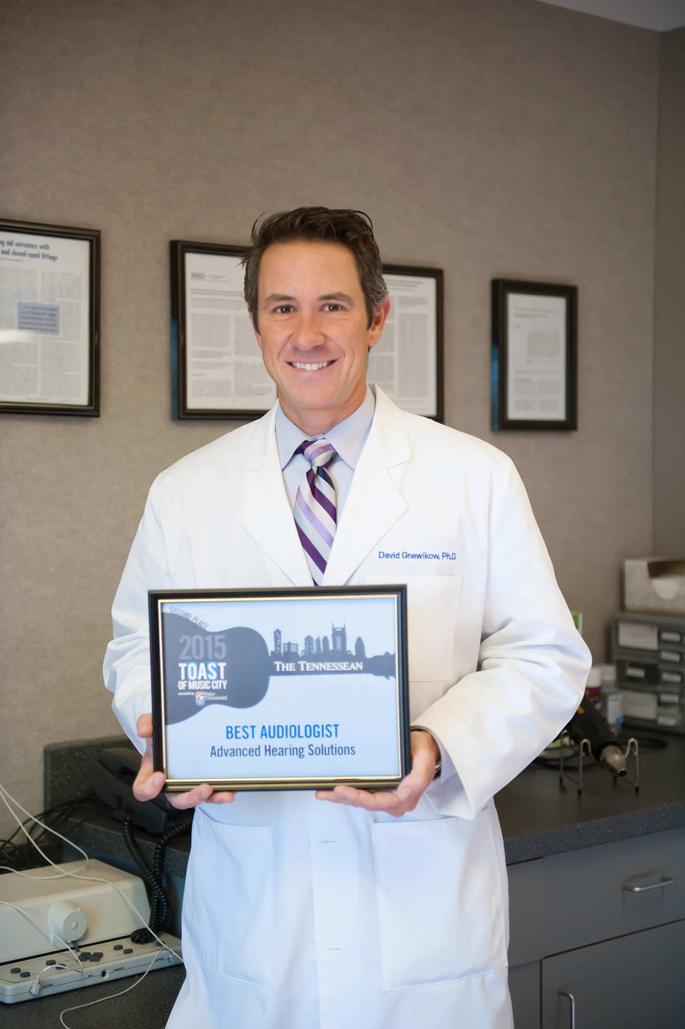 Dr. David Gnewikow holding his Tennessean Award for Best Audiologist