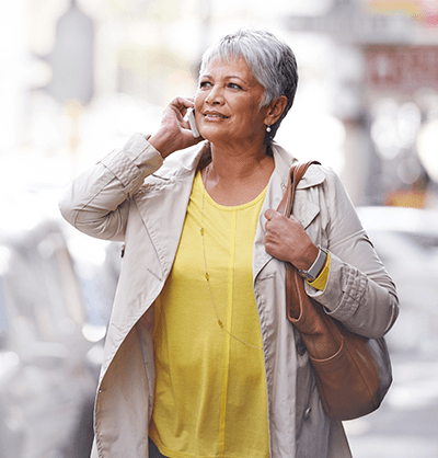 Older woman coping with background noise while on the phone