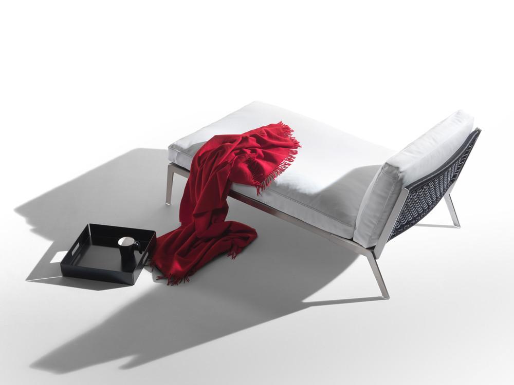 Happy. La poltrona dalla seduta lunga. Una sciarpa rossa e un vassoio dipingono una scena vissuta.