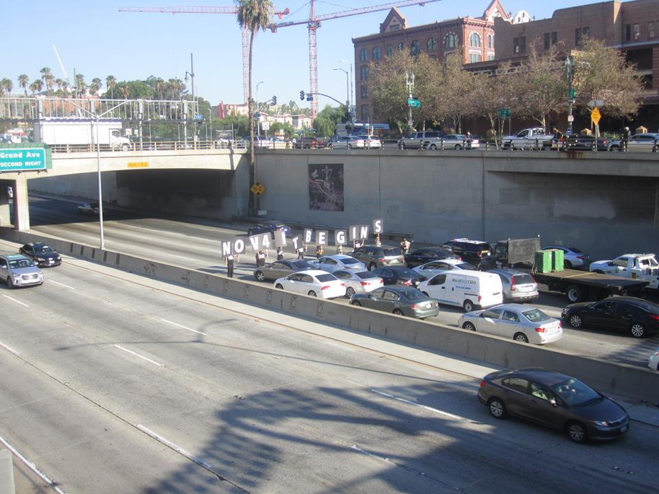 "Taking a knee on an LA freeway with ""Nov 4 It Begins"""