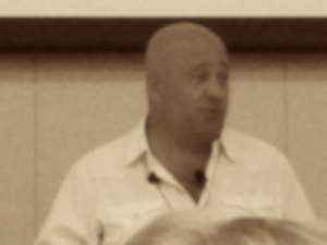 Andrew Zimmern speaking, sepia