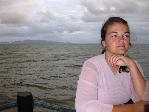 Lindsay on New Year's Eve at Uprising in Fiji, sitting beside the ocean