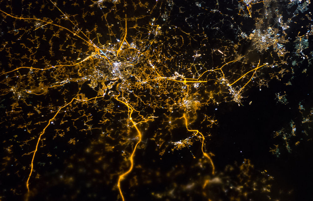 The brightly lit core of the Liège urban area appears to lie at the center of a network of roadways—traceable by continuous orange lighting—extending outwards into the rural, and relatively dark, Belgium countryside; Liège is on the left, Aachen on the right. Between the two, Verviers (left) and Eupen (right). The city of Spa is a bit lower, nearby the Hautes Fagnes protected area (no light). Photo by ISS Crew Earth Observations