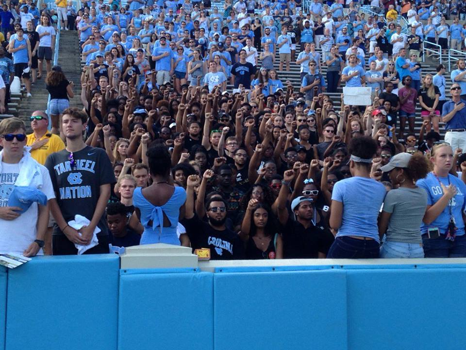 Students sit and raise fists in solidarity during anthem. Photo: Brian Hall
