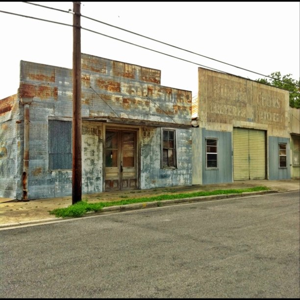 "Roadtrip adventures, continued … This pair of attached buildings in Shiner, Texas, just earned my top spot for favorite ghost sign, so far. The building on the left, covered in nailed-on sheets of painted tin, says, among other things, ""Feed Store,"" ""Purina Chows,"" and ""BABY CHICKS."" The building on the right was a ""hatchery,"" per its sign. Seriously awesome, no?"