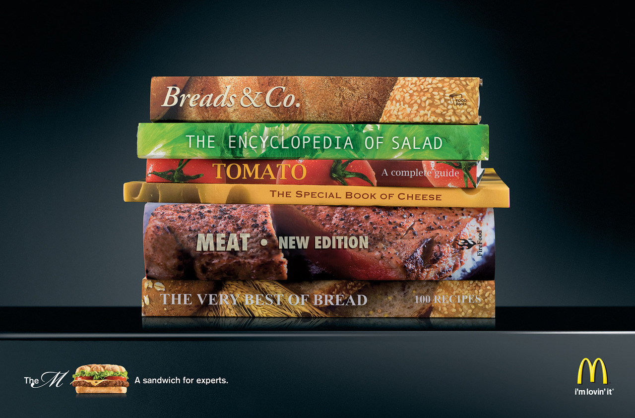 "Via newsweek: thedailywhat: Print Ad of the Day: McDonald's promotes a high-brow burger called ""The M"" with a stack of faux-books arranged to resemble a cheeseburger. [copyranter.] This is actually kind of genius."