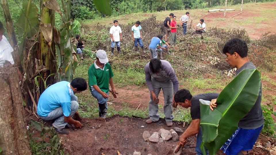 Die Bürger von Alto Tiwinza jäten Unkraut und graben Löcher für die Setzlinge.