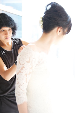 Chinese bride putting on wedding dress