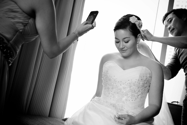 Hong Kong wedding bride putting on wedding dress