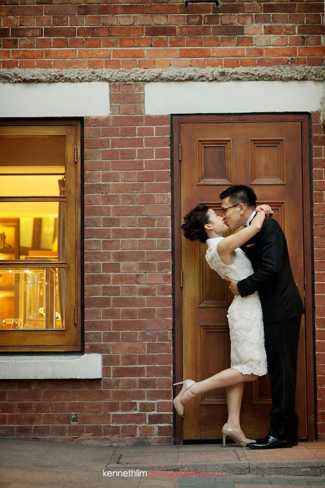 Hong Kong 1881 Heritage engagement photoshoot bride kissing groom at doorway
