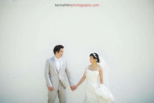 Koh Samui wedding YL Residence bride and groom portrait holding hands in front of white wall