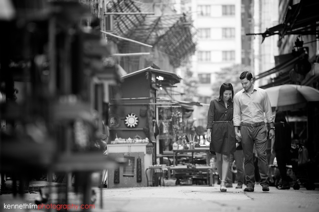 Hong Kong engagement photoshoot outdoors couple walking down street looking down black and white