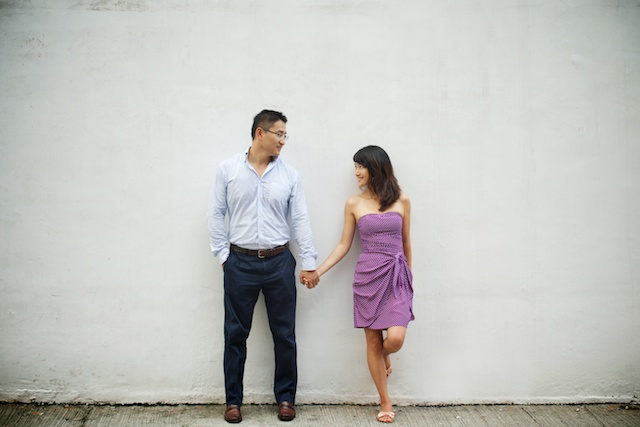 Hong-Kong-engagement-photoshoot-couple-holding-hands-leaning-against-wall-smiling