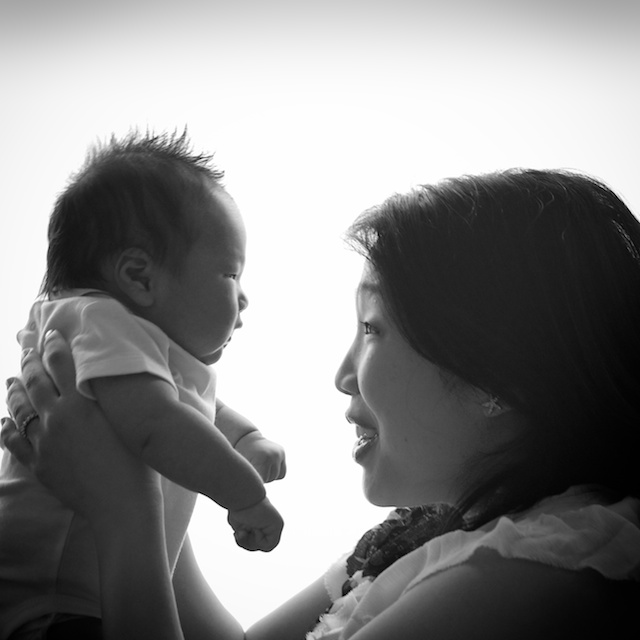 black and white photo of newborn baby boy and mother facing each other