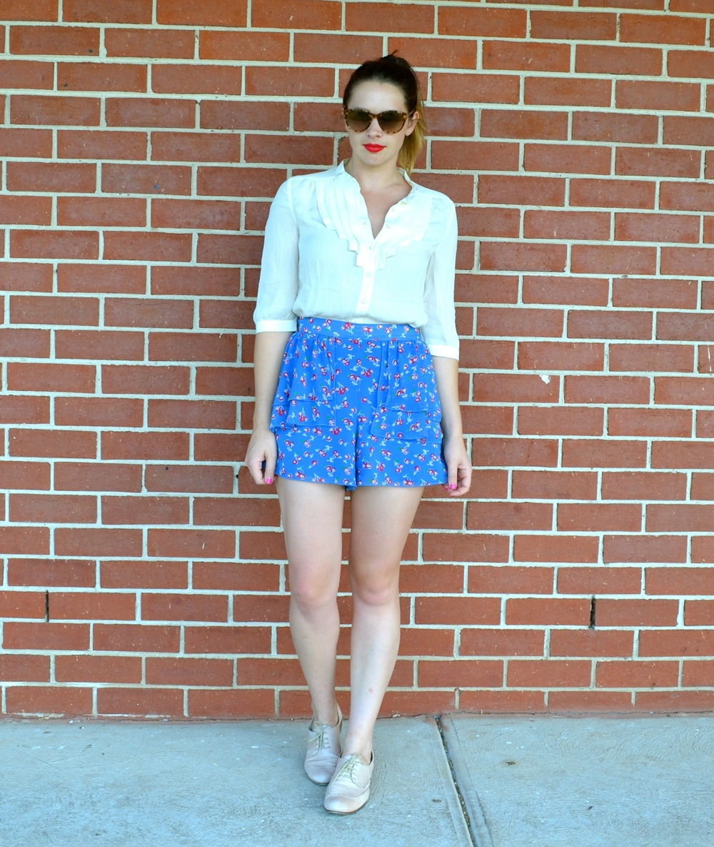 blue-shorts-white-blouse-brick-wall-oroton-sunglasses-leather-shoes