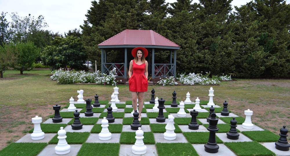 life-size-chess-set-pieces-red-dress-red-sun-hat
