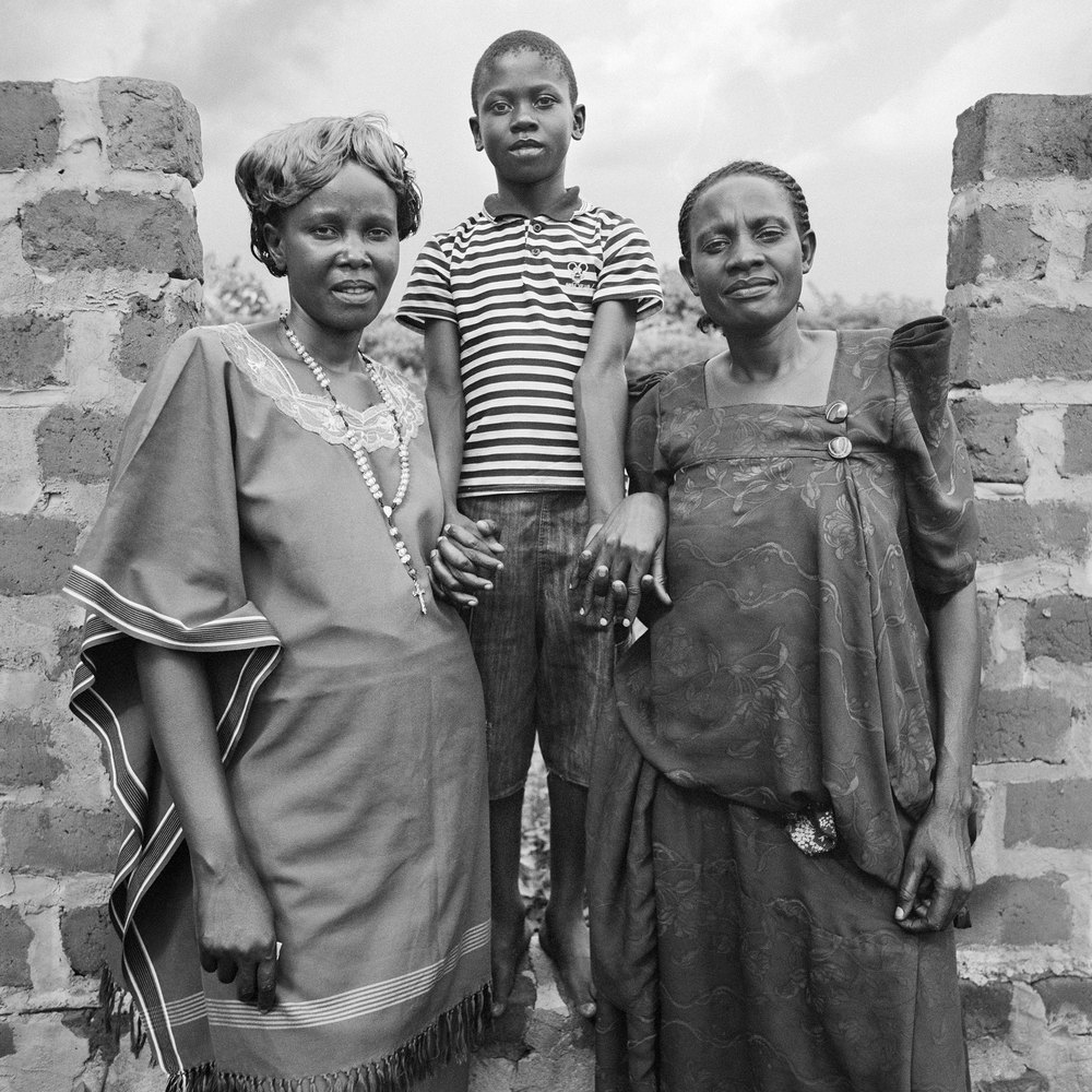 WPC members (from left to right) Anyango Florence, Mpiima Zacharious, and Athieno Vena.  These two women are sisters who have joined together to form a nontraditional family. They are raising their nephew in the middle, Mpiima, as their own son because he lost both of his parents at a young age. Both Florence and Vena are teachers at BESO Junior School and Mpiima excels in his studies thanks to their support.