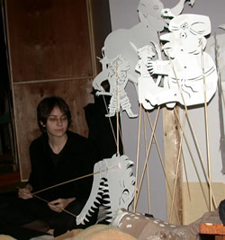 I was lucky to have a student (Chelsea Cook) with the ability to render puppets that respectfully quoted Indonesian demons and the costume designs of our live actors, while maintaining her own consistent style.  Pictured: Demon head puppet in her hand, fat Matavya in foreground. King and Matali and their chariot in the midground, with elephant in background.