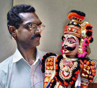 K.V. Ramesh, director of Sri Gopalakrishna Yakshagana Bombeyata Sangha, Kasaragod, with a puppet