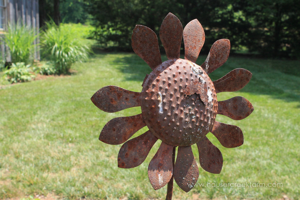 Rusty metal sculpture of sunflower with missing petal in green yard
