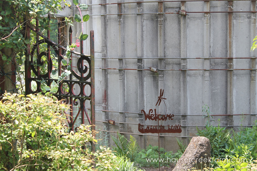Plants, flowers and iron gate by silo with rustic welcome sign