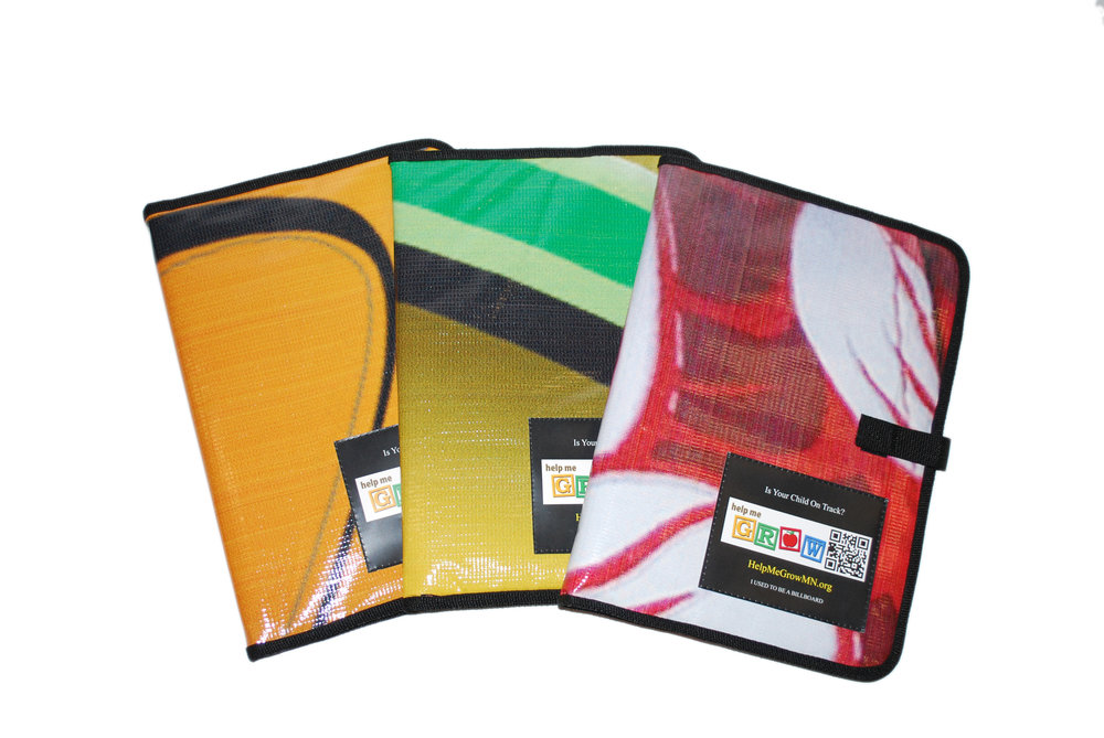 Colorful padfolios made from repurposed materials that holds notebooks, pens, and documents