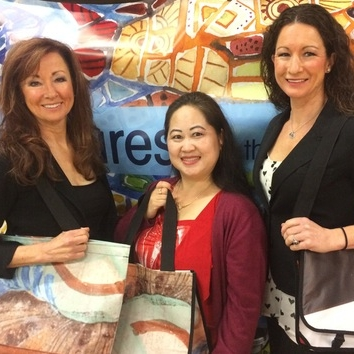 Della Simpson Kari Brizius and Pan Kou one of our sewers show off upcycled banner and billboard totes