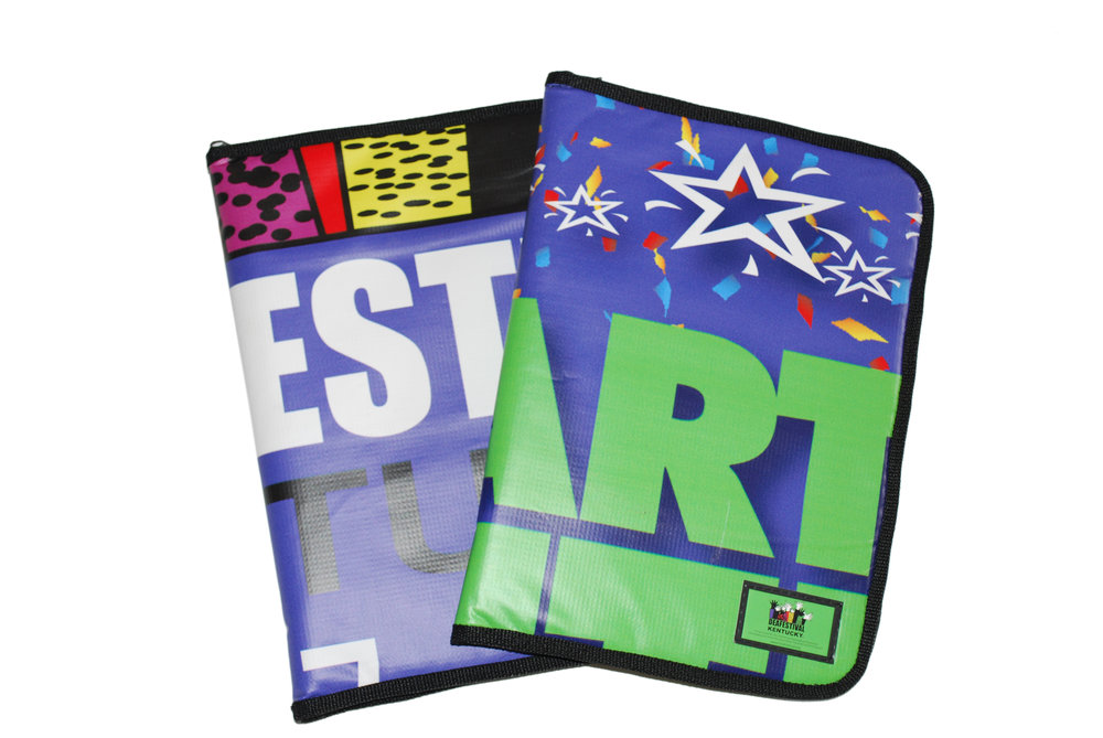 Colorful, full-size padfolios made from repurposed banners or billboards that can hold a pad of paper, pen, and files