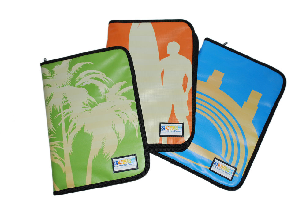Large padfolios made from repurposed banners and billboards that can hold pad of paper, pen, and documents