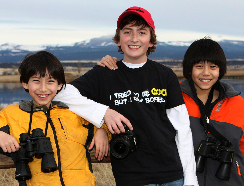 three children outside near mountains together