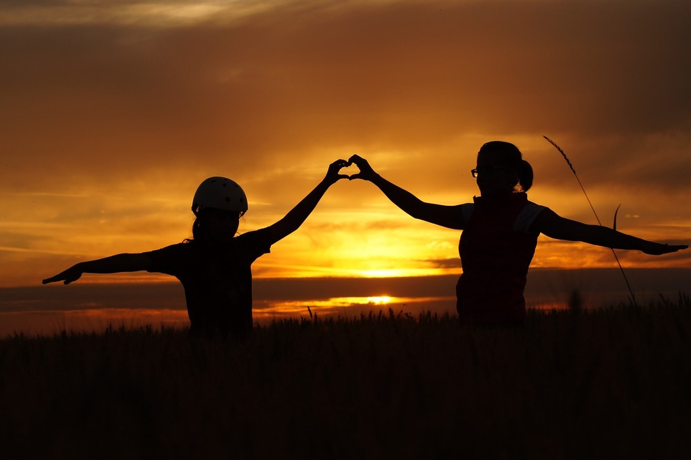 two teenagers in front of the sunset with their hands together making a heart