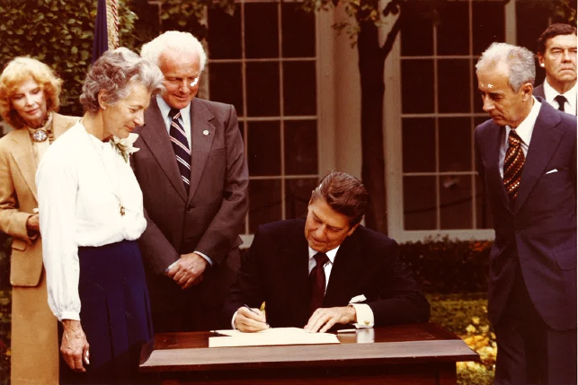 Congressman Tom Lantos, Nina Lagergren, and Guy von Dardel look on as President Reagan signs legislation authored by Congressman Lantos making Raoul an Honorary US Citizen. October, 1981.