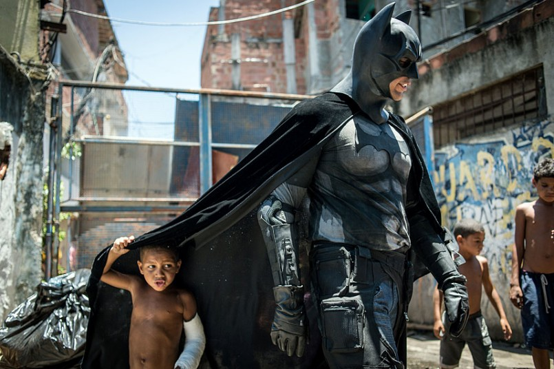 inothernews :      Children play around a man disguised as Batman at the Favela do Metro slum, an area close to the Maracana stadium, in Rio de Janeiro, Brazil. Families living in this shantytown have refused to have their homes demolished as part of a project to renovate the district before the FIFA World Cup in June.   (Photo: Yasuyoshi Chiba / AFP via The Telegraph)