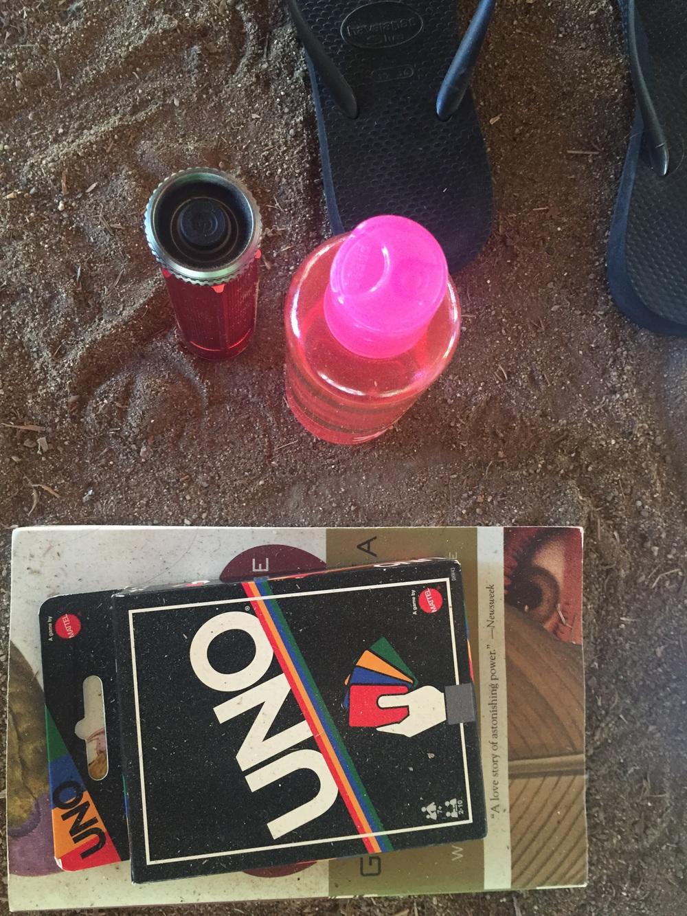 Deserted beach necessities; Uno, Gabriel Garcia Marquez, Haivainas, flashlight, and coconut oil