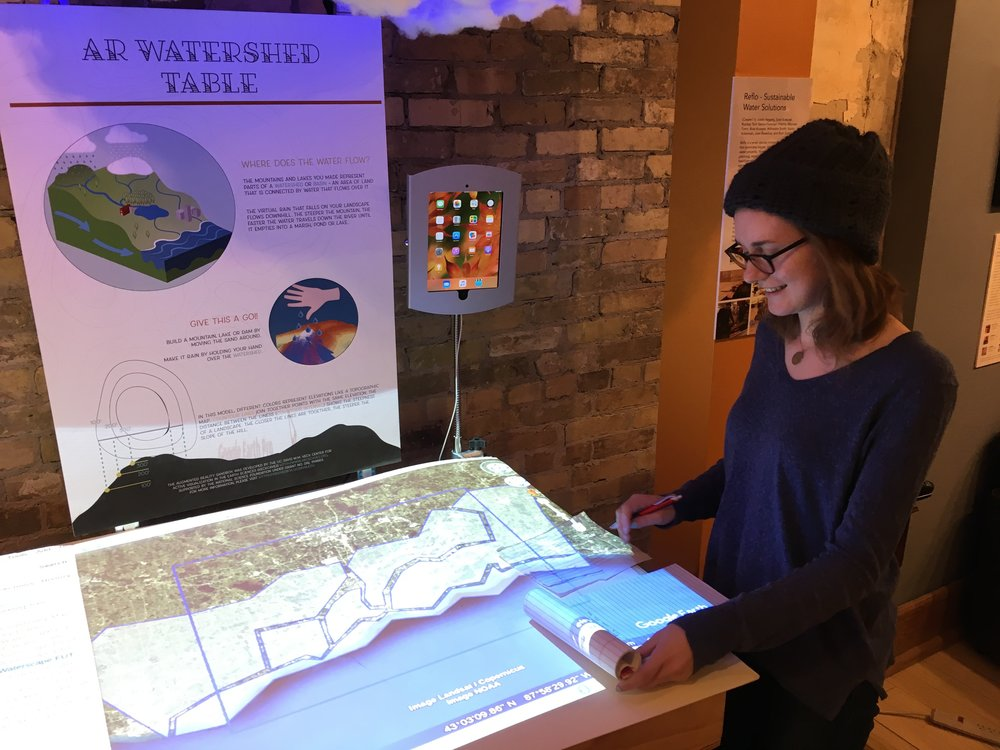 Game designer Bryn Summers considers the balance between user interface and art assets for MKE Waterscape on the AR Table.