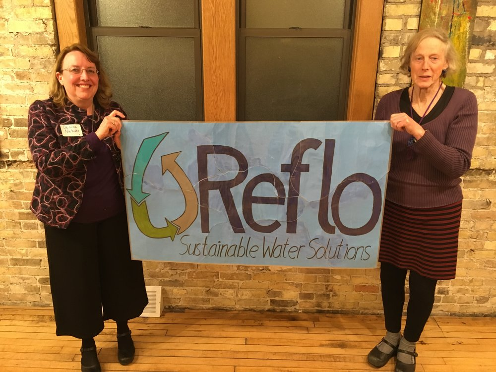 Board members Denice Niebuhr and Barbara Ricahrds hold the Reflo puzzle-piece banner after the annual advisory council dinner held at Arts @ Large on March 21. Notes and feedback from seven break-out groups was written on the back of each piece of the puzzle.