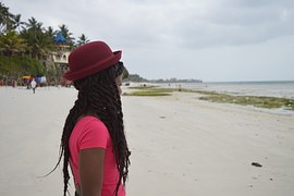 On the beach in pink rockin  jumbo Senegalese twists and dapper hat.