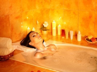 Woman relaxing in hot bubble bath with candles