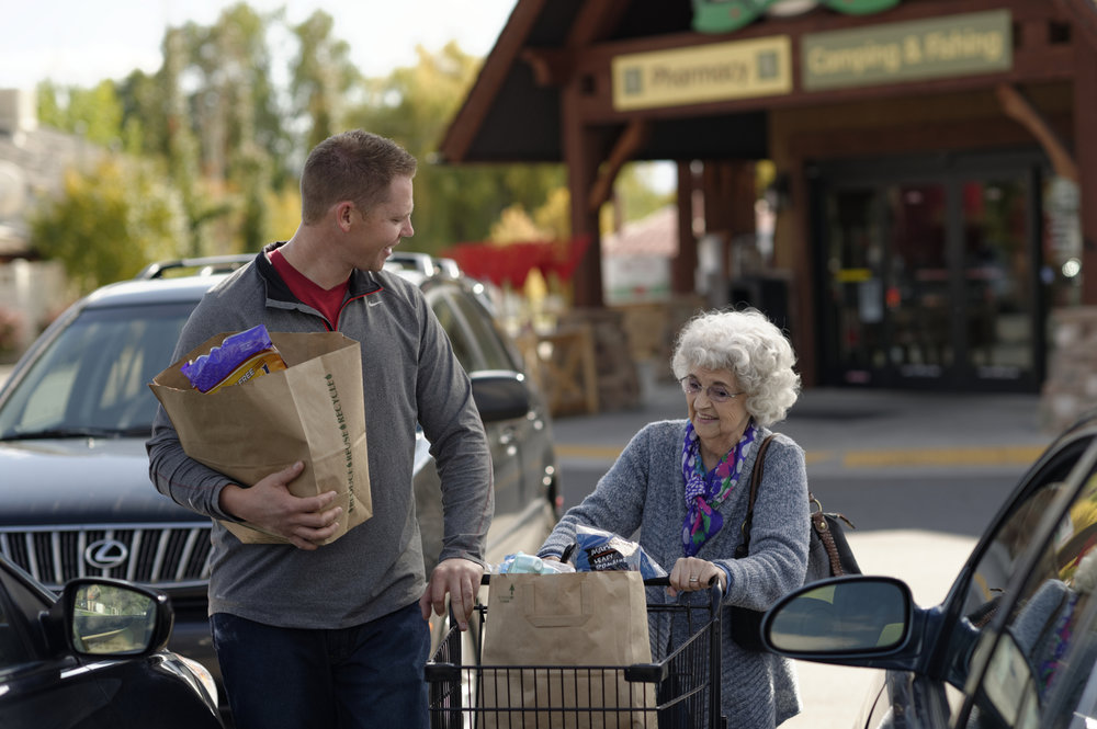 man-helping-elderly-woman-groceries-.jpg