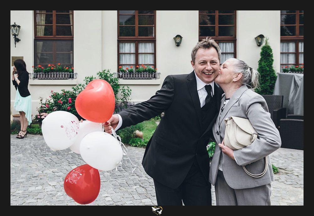 Bräutigam mit Luftballons und Mutter