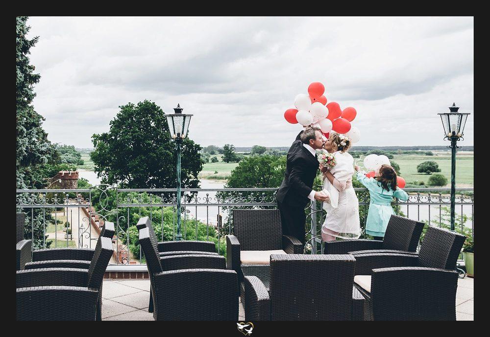 Kuss des Brautpaares mit Ballons
