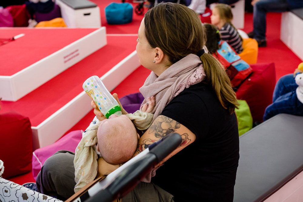 Mutter gibt Baby Flasche auf der Babywelt Messe