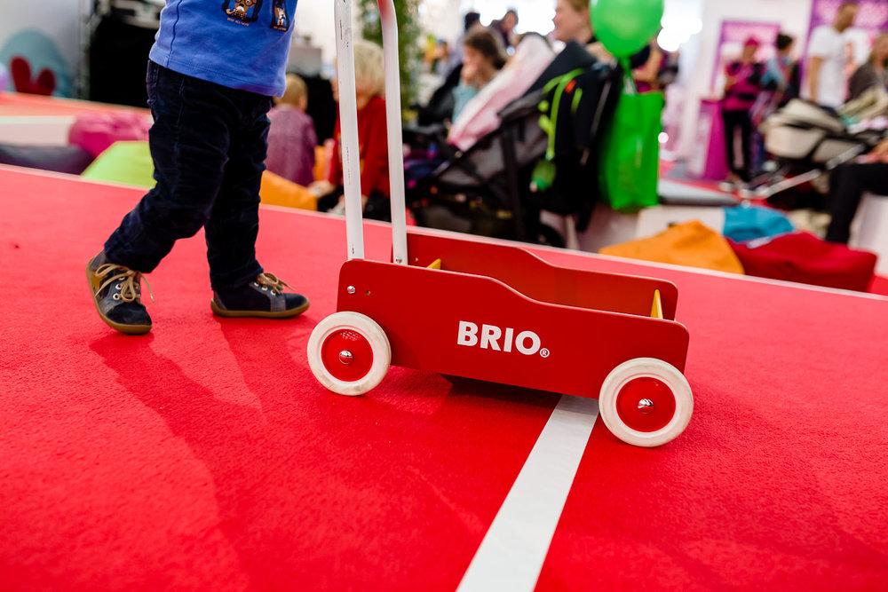 Kind mit Brio Lauflernwagen fährt über Ziellinie