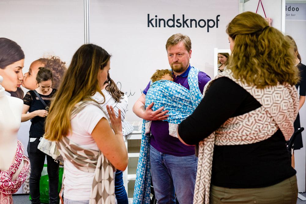 Mann probiert Baby-Trageschal am Stand von Kindsknopf