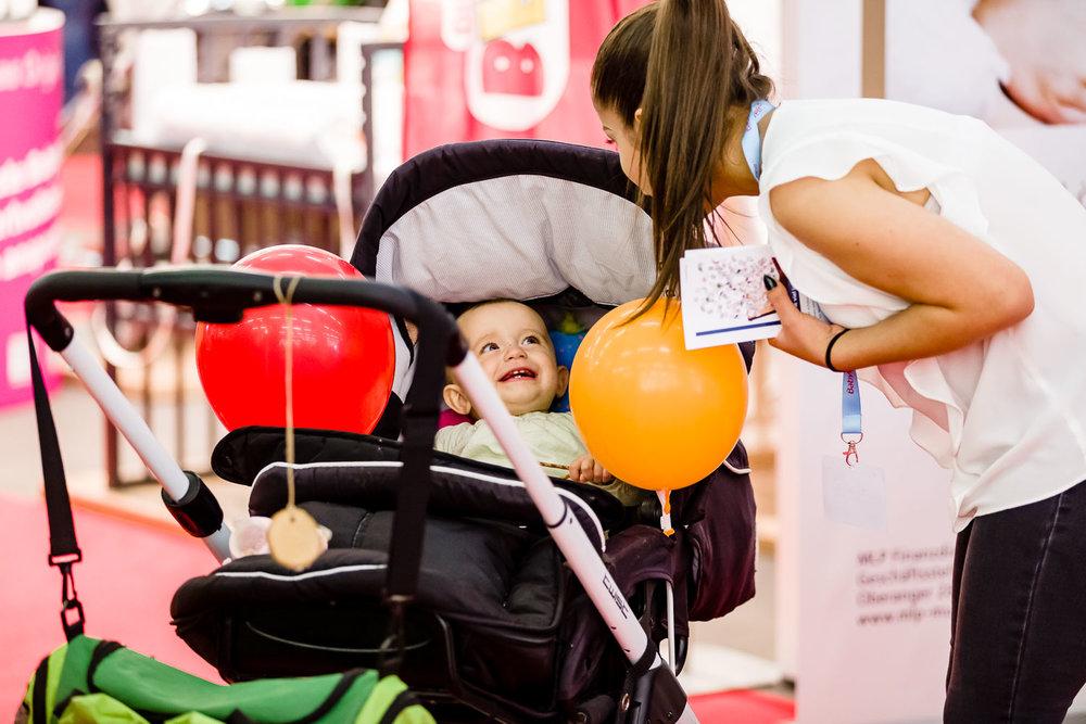 Baby im Kinderwagen lacht Frau auf der Babywelt Messe München an, die in den Wagen schaut.Foto: Peter Meyer www.für-immer-mein.com