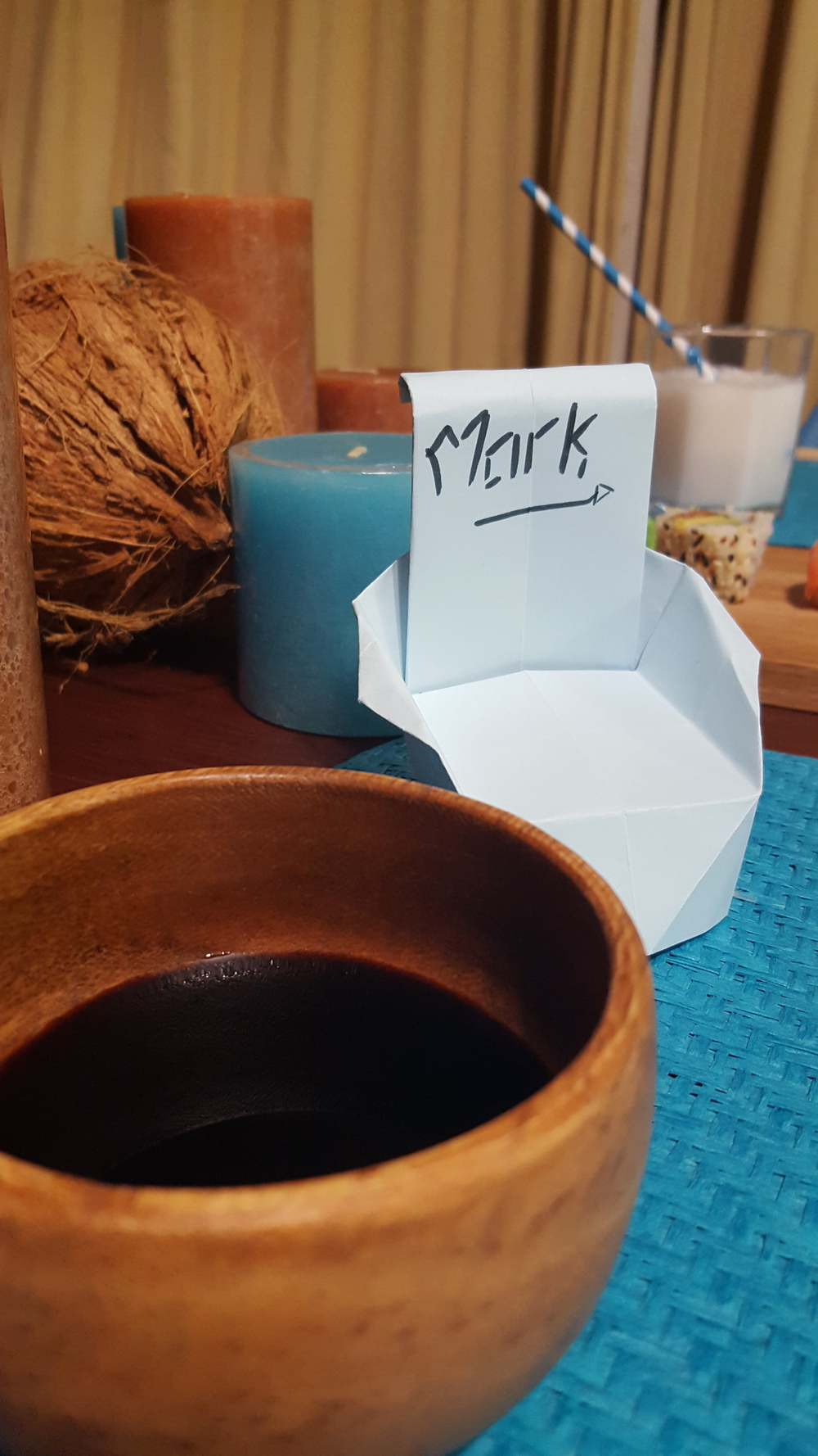 wooden soy sauce bowl, origami chair, coconut and candles in blue and brown for Japanese table setting