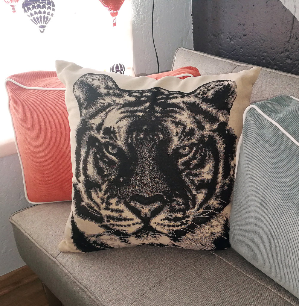 Tiger pillow on colourful turqouise pillows in colourful travel themed nursery and baby room by Tassels & Tigers interior decor and design.jpg