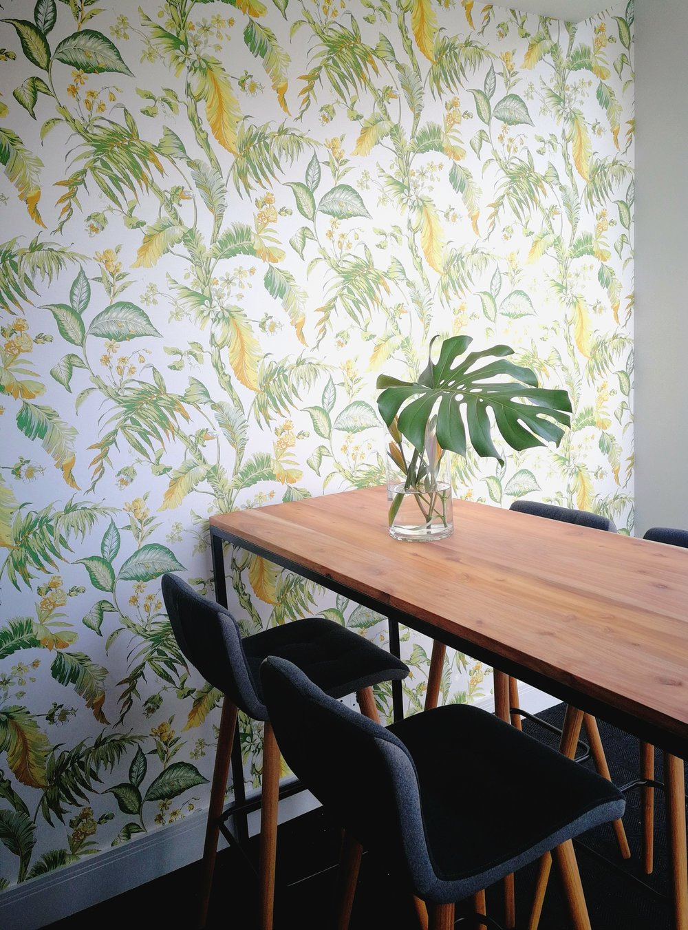 A corporate green room in Rosebank, Johannesburg, with a tropical wallpaper installation by Tassels & Tigers Interiors